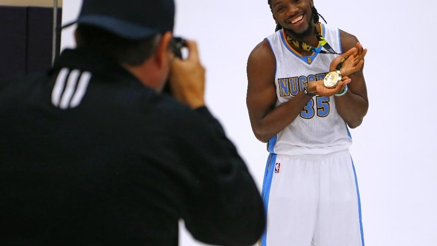 Denver Nuggets' Kenneth Faried poses with his FIBA basketball world cup gold medal during NBA basketball media day, Monday, Sept. 29, 2014, in Denver. (AP Photo/Jack Dempsey)