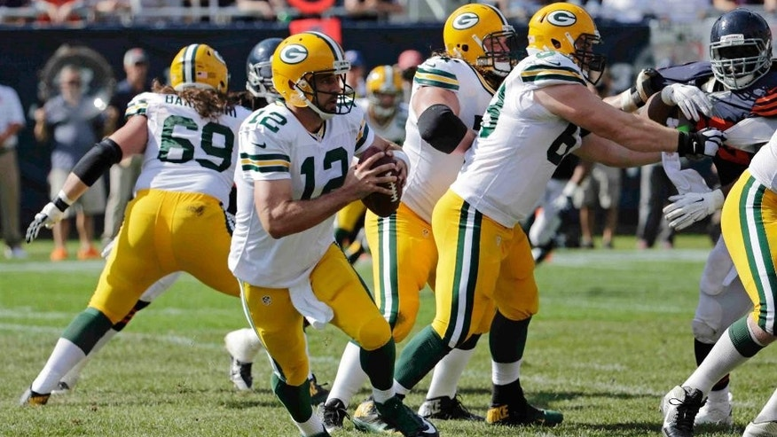 Green Bay Packers quarterback Aaron Rodgers (12) drops back to pass in the second half of an NFL football game against the Chicago Bears Sunday, Sept. 28, 2014, in Chicago. (AP Photo/Charles Rex Arbogast)