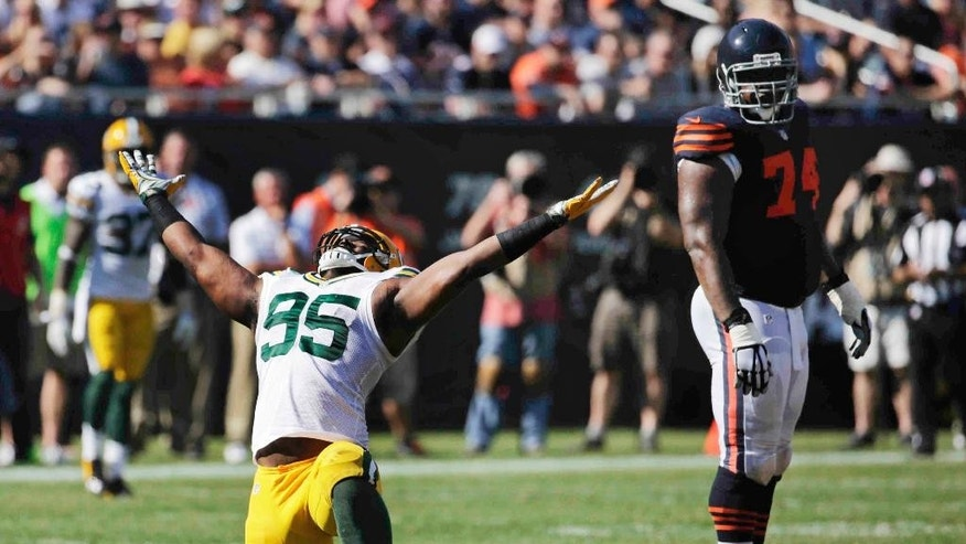 Green Bay Packers defensive end Datone Jones (95) celebrates after sacking Chicago Bears quarterback Jay Cutler in the second half of an NFL football game Sunday, Sept. 28, 2014, in Chicago. At right is Bears tackle Jermon Bushrod (74). The Packers won 38-17. (AP Photo/Charles Rex Arbogast)