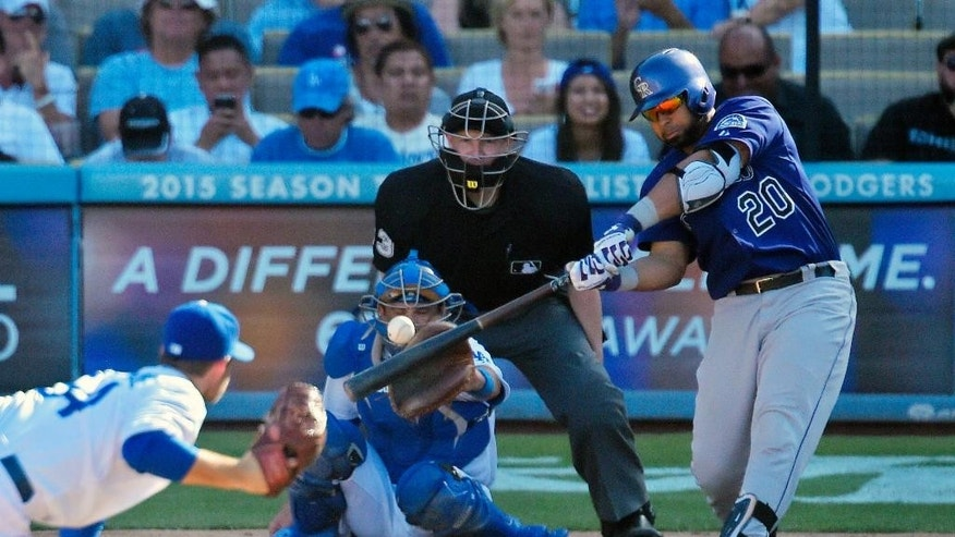 Colorado Rockies' Wilin Rosario, right, hits a solo home run as Los Angeles Dodgers relief pitcher Daniel Coulombe, left, looks on along with catcher Drew Butera, second from left, and home plate umpire Mike Estabrook during the eighth inning of a baseball game, Sunday, Sept. 28, 2014, in Los Angeles. (AP Photo/Mark J. Terrill)