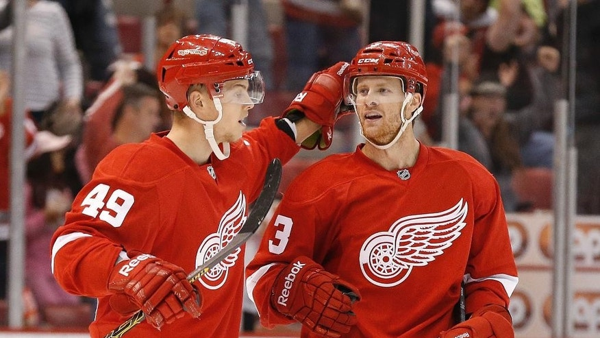 Detroit Red Wings defenseman Nick Jensen (3) celebrates his goal against the Toronto Maple Leafs with Andrej Nestrasil (49), of the Czech Republic, in the second period of a NHL hockey game in Detroit Monday, Sept. 29, 2014. (AP Photo/Paul Sancya)