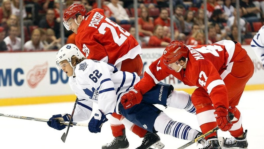 Detroit Red Wings defenseman Alexei Marchenko (47), of Russia, knocks Toronto Maple Leafs right wing William Nylander (62) off the puck in the first period of a NHL hockey game in Detroit Monday, Sept. 29, 2014. (AP Photo/Paul Sancya)