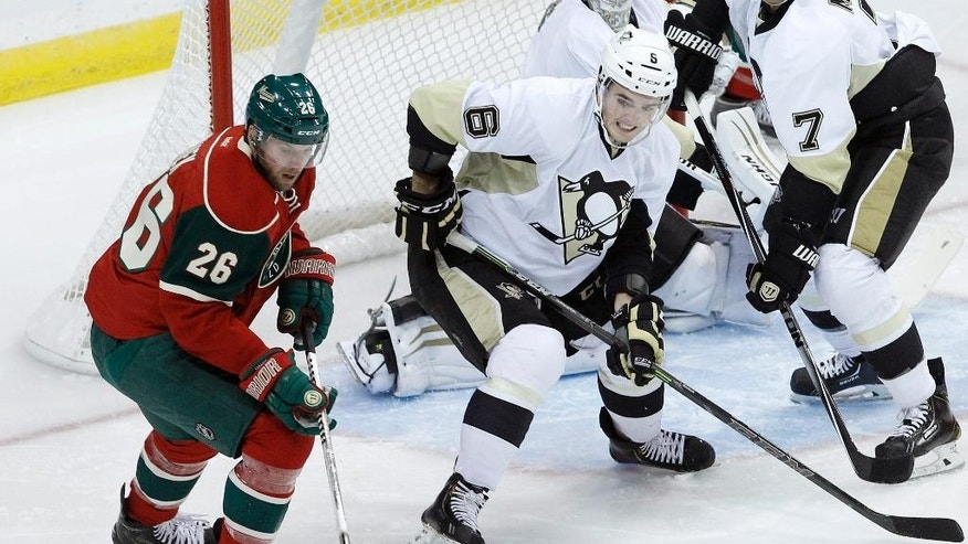 Minnesota Wild left wing Thomas Vanek (26), of Austria, and Pittsburgh Penguins defenseman Scott Harrington (6) chase the puck during the first period of a preseason NHL hockey game in St. Paul, Minn., Monday, Sept. 29, 2014. (AP Photo/Ann Heisenfelt)