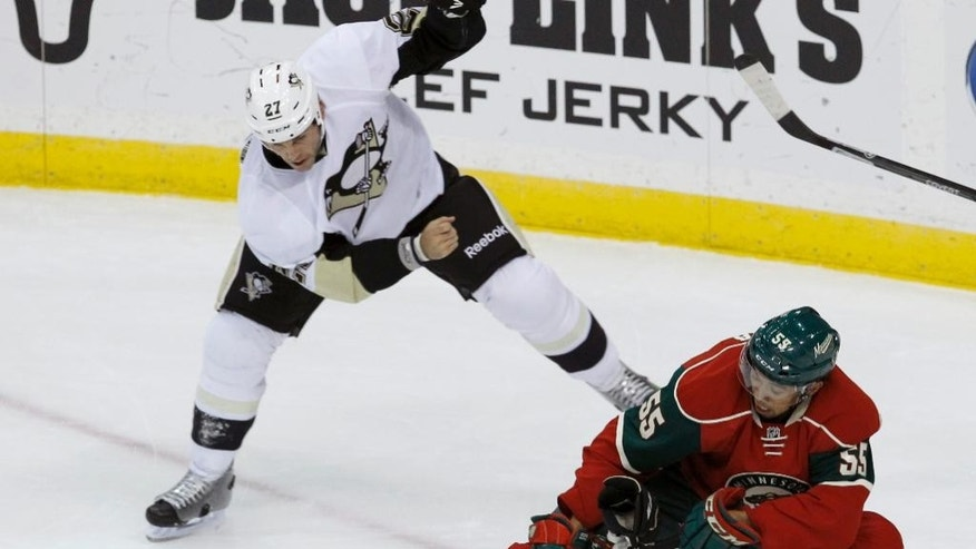 Minnesota Wild defenseman Mathew Dumba (55) and Pittsburgh Penguins right wing Craig Adams (27) chase the puck during the first period of a preseason NHL hockey game in St. Paul, Minn., Monday, Sept. 29, 2014. (AP Photo/Ann Heisenfelt)