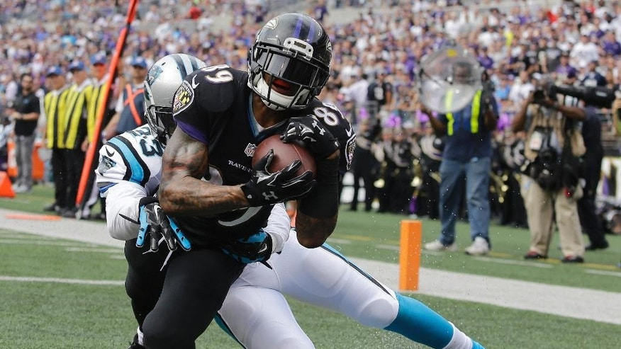 Baltimore Ravens running back Justin Forsett (29) steps away Carolina Panthers strong safety Roman Harper (41) and into the end zone for a touchdown during the first half of an NFL football game in Baltimore, Sunday, Sept. 28, 2014. (AP Photo/Evan Vucci)