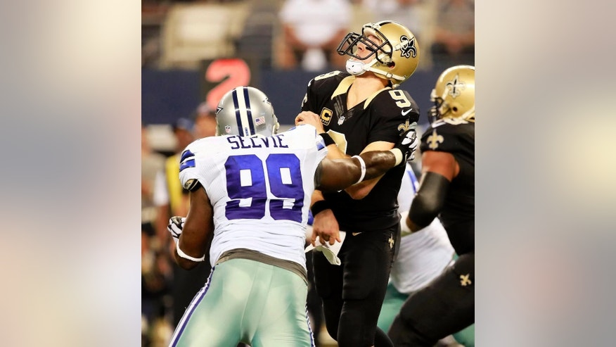 New Orleans Saints quarterback Drew Brees (9) is tackled by Dallas Cowboys defensive end George Selvie (99) during the second half of an NFL football game Sunday, Sept. 28, 2014, in Arlington, Texas. (AP Photo/The Waco Tribune-Herald, Jose Yau)