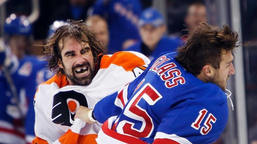 Philadelphia Flyers' Zack Stortini, left, fights with New York Rangers' Tanner Glass (15) during the first period of an NHL preseason hockey game Monday, Sept. 29, 2014, in New York. (AP Photo/Jason DeCrow)