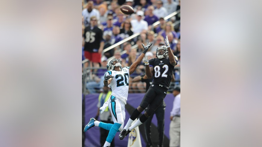 Baltimore Ravens wide receiver Torrey Smith (82) pulls in a touchdown pass under pressure from Carolina Panthers cornerback Antoine Cason (20) during the second half of an NFL football game in Baltimore, Sunday, Sept. 28, 2014. (AP Photo/Gail Burton)