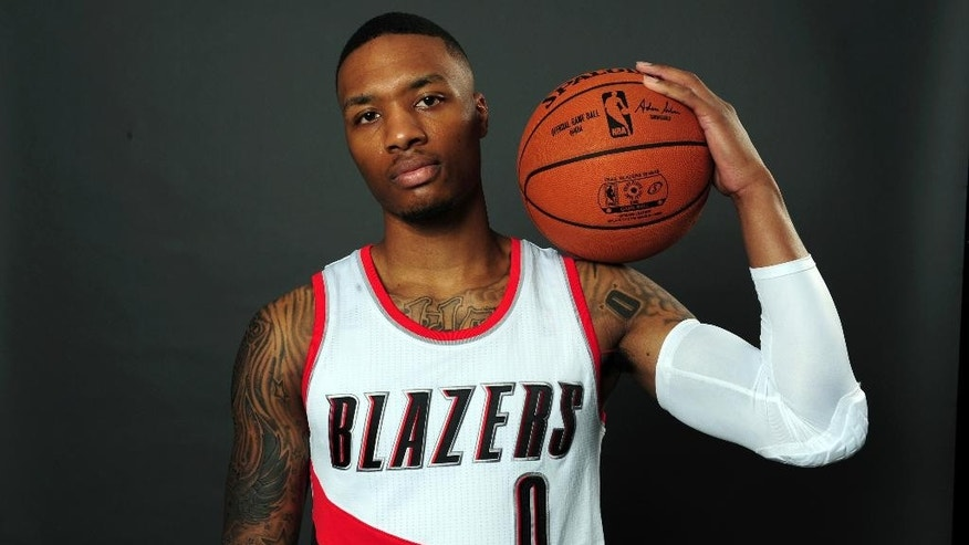 Portland Trail Blazers guard Damian Lillard (0) poses for a photograph during media day in Portland, Ore., Monday, September 29, 2014. (AP Photo/Steve Dykes)