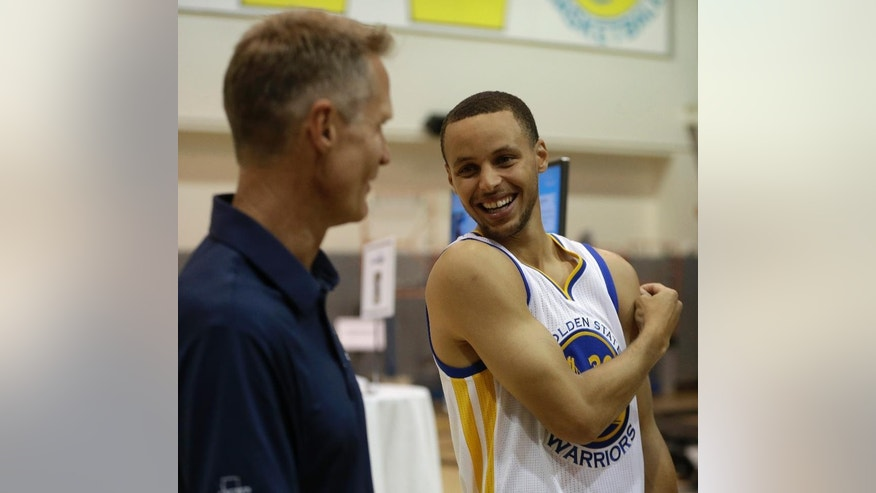 Golden State Warriors' Stephen Curry, right, speaks with coach Steve Kerr during NBA basketball media day, Monday, Sept. 29, 2014, in Oakland, Calif. (AP Photo/Ben Margot)
