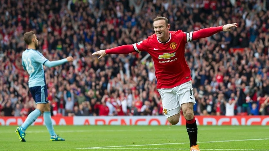 Manchester United's Wayne Rooney, right, celebrates after scoring against West Ham United during their English Premier League soccer match at Old Trafford Stadium, Manchester, England, Saturday Sept. 27, 2014. (AP Photo/Jon Super)