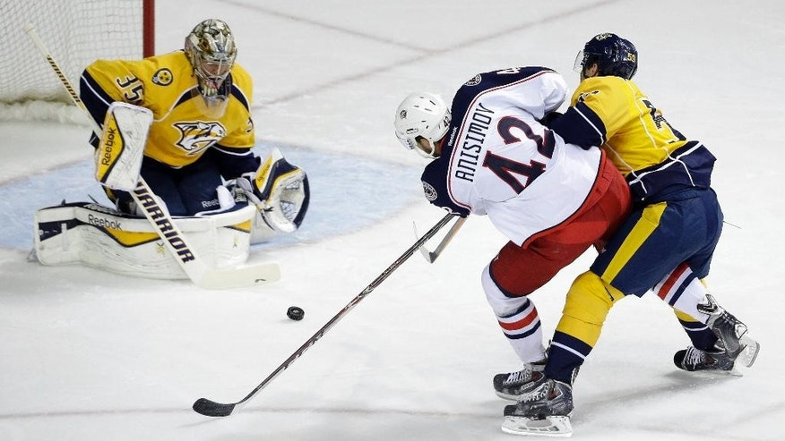 Nashville Predators goalie Pekka Rinne (35), of Finland, blocks a shot by Columbus Blue Jackets center Artem Anisimov (42), of Russia, in the first period of a preseason NHL hockey game Monday, Sept. 29, 2014, in Nashville, Tenn. Defending at right is Nashville Predators defenseman Roman Josi, of Switzerland. (AP Photo/Mark Humphrey)
