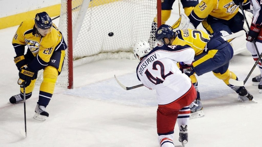 Columbus Blue Jackets center Artem Anisimov (42), of Russia, scores between Nashville Predators' Anton Volchenkov (20), of Russia, and Paul Gaustad (28) in the first period of a preseason NHL hockey game Monday, Sept. 29, 2014, in Nashville, Tenn. (AP Photo/Mark Humphrey)