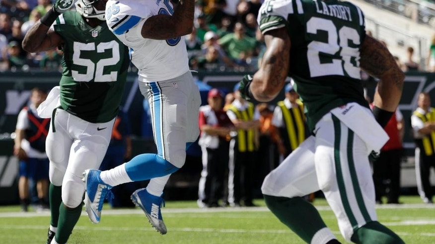 Detroit Lions tight end Eric Ebron, center, pulls in a touchdown reception as New York Jets inside linebacker David Harris (52) and strong safety Dawan Landry (26) defend on the play during the first half of an NFL football game, Sunday, Sept. 28, 2014, in East Rutherford, N.J. (AP Photo/Frank Franklin II)