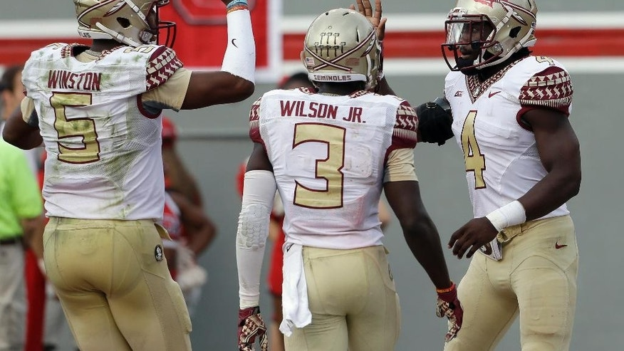 Florida State's Jameis Winston (5), Jesus Wilson (3) and Dalvin Cook (4) celebrate Cook's touchdown against North Carolina State during the second half of an NCAA college football game in Raleigh, N.C., Saturday, Sept. 27, 2014. Florida State won 56-41.(AP Photo/Gerry Broome)