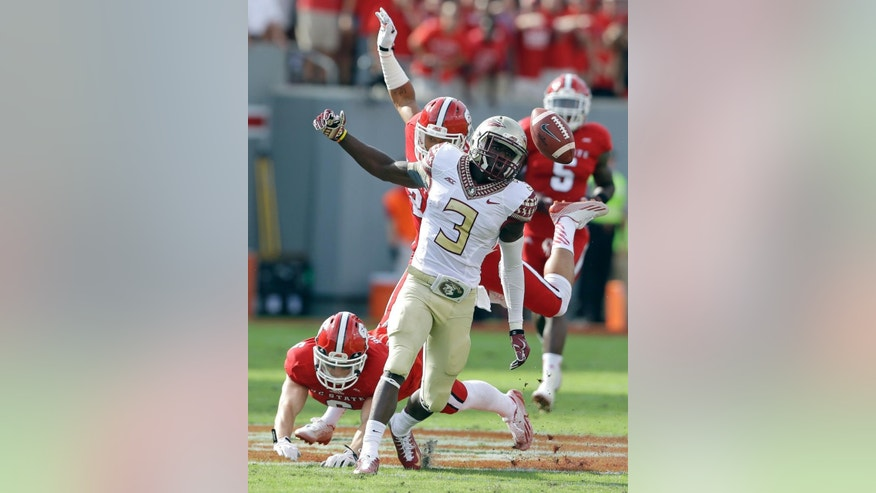 Florida State's Jesus Wilson (3) misses a pass as North Carolina State's Josh Jones, rear, and Tim Buckley defend during the first half of an NCAA college football game in Raleigh, N.C., Saturday, Sept. 27, 2014. (AP Photo/Gerry Broome)