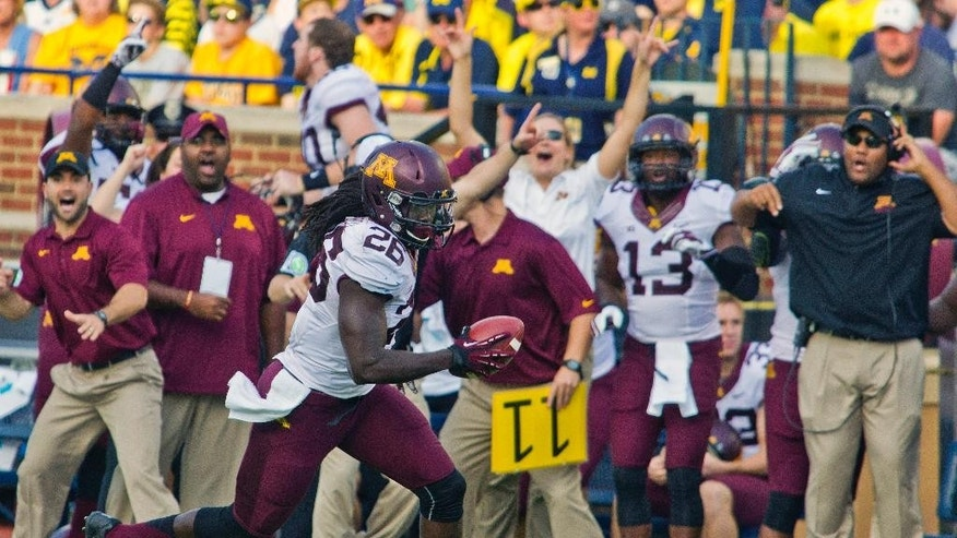 Minnesota linebacker De'Vondre Campbell (26) rushes for a touchdown after intercepting a Michigan pass in the third quarter of an NCAA college football game in Ann Arbor, Mich., Saturday, Sept. 27, 2014. Minnesota won 30-14. (AP Photo/Tony Ding)