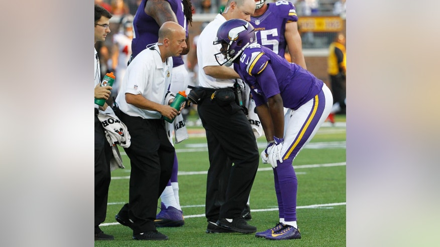 FILE - In this Sunday, Sept. 28, 2014, file photo, Minnesota Vikings quarterback Teddy Bridgewater talks to a trainer after getting injured in the second half of an NFL football game against the Atlanta Falcons in Minneapolis. Bridgewater's first start for the Vikings couldn't have been better, except of course for the sprained left ankle in the fourth quarter that forced him out of the 41-28 victory over Atlanta.(AP Photo/Ann Heisenfelt, File)