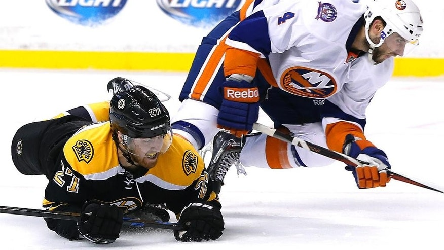 Boston Bruins defenseman Dougie Hamilton (27) slides on the ice after colliding with New York Islanders defenseman T.J. Brennan (4) during the second period of an NHL preseason hockey game in Boston, Tuesday, Sept. 30, 2014. The Islanders won 5-3. (AP Photo/Elise Amendola)