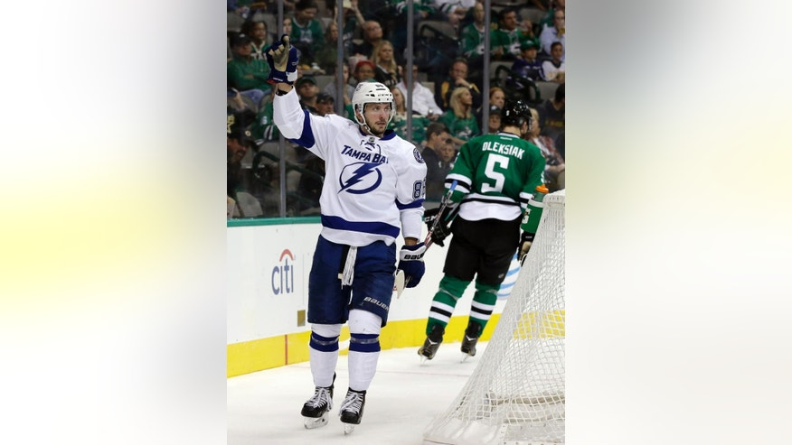 Tampa Bay Lightning's Nikita Kucherov (86), of Russia, celebrates his goal as Dallas Stars' Jamie Oleksiak (5) skates back to the bench during the second period of a preseason NHL hockey game, Tuesday, Sept. 30, 2014, in Dallas. (AP Photo/Tony Gutierrez)