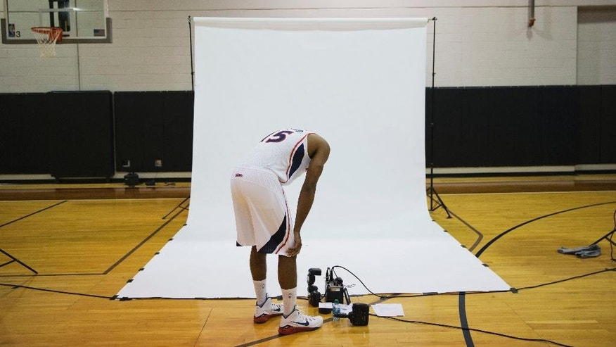 Atlanta Hawks' Al Horford bends over to look at a photographer's camera equipment while waiting his turn to have his official NBA picture taken during NBA basketball media day, Monday, Sept. 29, 2014, in Atlanta. (AP Photo/David Goldman)