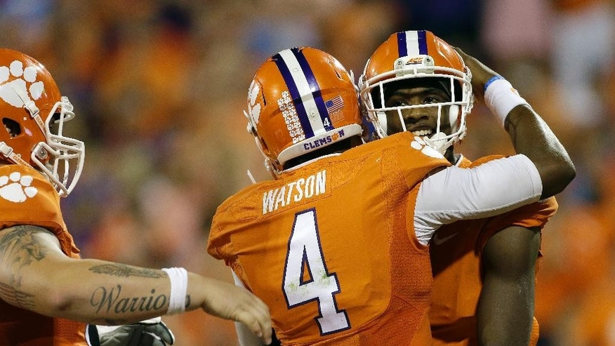 Clemson's Deshaun Watson, left, hugs teammate, Mike Williams, right, after Williams scored one of his multiple touchdowns against North Carolina during the second half of an NCAA college football game in Clemson, S.C., Saturday Sept. 27, 2014. Clemson won 50-35. (AP Photo/Bob Leverone)