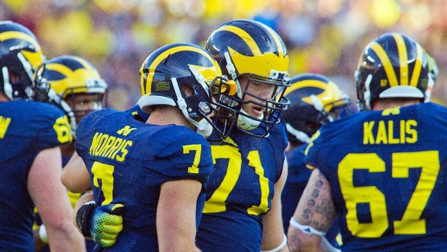 In this Sept. 27, 2014, photo, Michigan quarterback Shane Morris (7) leans against offensive lineman Ben Braden (71) after taking a hit in the fourth quarter of an NCAA college football game against Michigan in Ann Arbor, Mich. Early Tuesday, Sept. 30, 2014, roughly 12 hours after embattled Michigan coach Brady Hoke said he'd been given no indication that Morris had been diagnosed with a concussion, athletic director Dave Brandon revealed in a post-midnight statement that the sophomore did appear to have sustained one.  (AP Photo/Tony Ding)