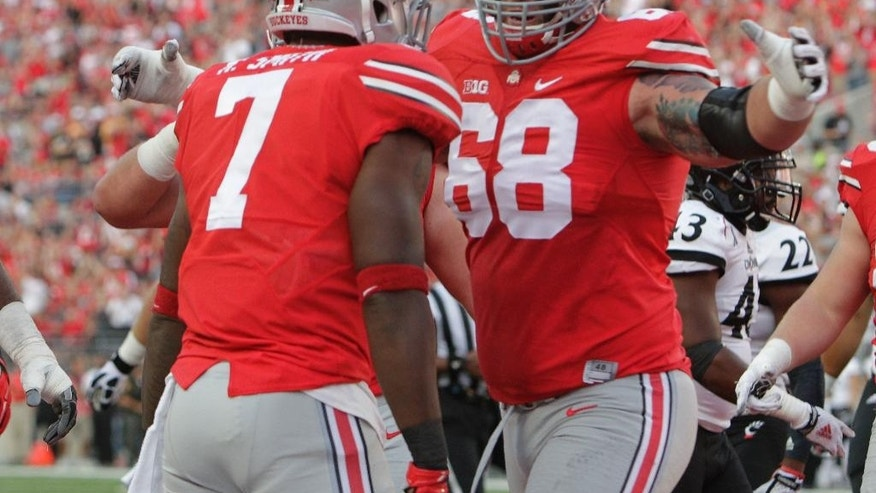 Ohio State running back Rod Smith, left, celebrates his touchdown against Cincinnati with teammate offensive lineman Taylor Decker during the first quarter of an NCAA college football game Saturday, Sept. 27, 2014, in Columbus, Ohio. (AP Photo/Jay LaPrete)