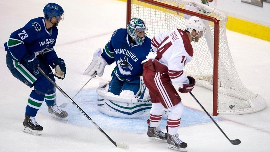Vancouver Canucks Alexander Edler (23) looks on after Arizona Coyotes Jeff Halpern (14) put a shot past Vancouver Canucks goalie Ryan Miller during the first period of an NHL hockey game in Vancouver, British Columbia, Monday, Sept. 29, 2014. (AP Photo/The Canadian Press, Jonathan Hayward)