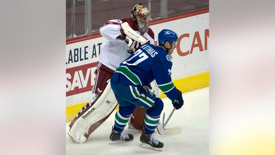 Vancouver Canucks center Shawn Matthias (27) tries to get around Arizona Coyotes goalie Mike Smith during the first period of an NHL hockey game in Vancouver, British Columbia, Monday, Sept. 29, 2014. (AP Photo/The Canadian Press, Jonathan Hayward)