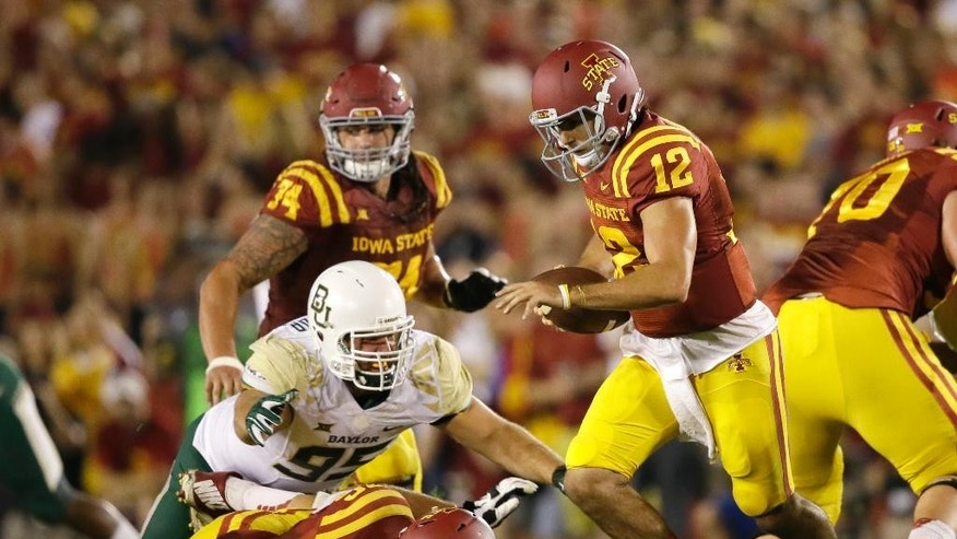 Iowa State quarterback Sam B. Richardson (12) runs from Baylor defensive lineman Beau Blackshear (95) during the first half of an NCAA college football game, Saturday, Sept. 27, 2014, in Ames, Iowa. (AP Photo/Charlie Neibergall)