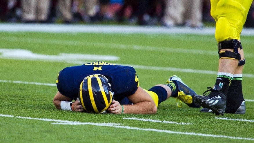 In this Sept. 27, 2014, photo, Michigan quarterback Shane Morris lays on the field after taking a hit in the fourth quarter of an NCAA college football game against Michigan in Ann Arbor, Mich. Early Tuesday, Sept. 30, 2014, roughly 12 hours after embattled Michigan coach Brady Hoke said he'd been given no indication that Morris had been diagnosed with a concussion, athletic director Dave Brandon revealed in a post-midnight statement that the sophomore did appear to have sustained one. (AP Photo/Tony Ding)