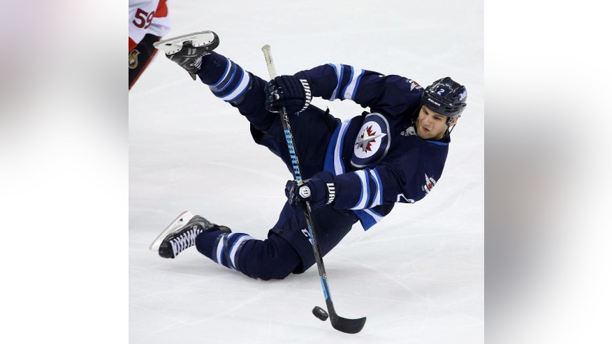 Winnipeg Jets' Adam Pardy plays the puck as he falls during the first period of a preseason NHL hockey game against the Ottawa Senators, Tuesday, Sept. 30, 2014, in Winnipeg, Manitoba. (AP Photo/The Canadian Press, Trevor Hagan)