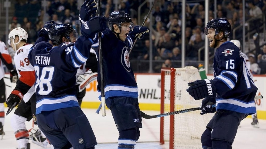 Winnipeg Jets' Nic Petan (38), Nikolaj Ehlers and Matt Halischuk (15) celebrate after Ehlers scored against the Ottawa Senators during the second period of a preseason NHL hockey game Tuesday, Sept. 30, 2014, in Winnipeg, Manitoba. (AP Photo/The Canadian Press, Trevor Hagan)