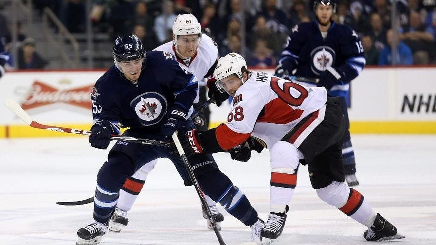 Winnipeg Jets' Mark Scheifele (55) competes with Ottawa Senators' Mark Stone (61) and Mike Hoffman (68) during the second period of a preseason NHL hockey game Tuesday, Sept. 30, 2014, in Winnipeg, Manitoba. (AP Photo/The Canadian Press, Trevor Hagan)