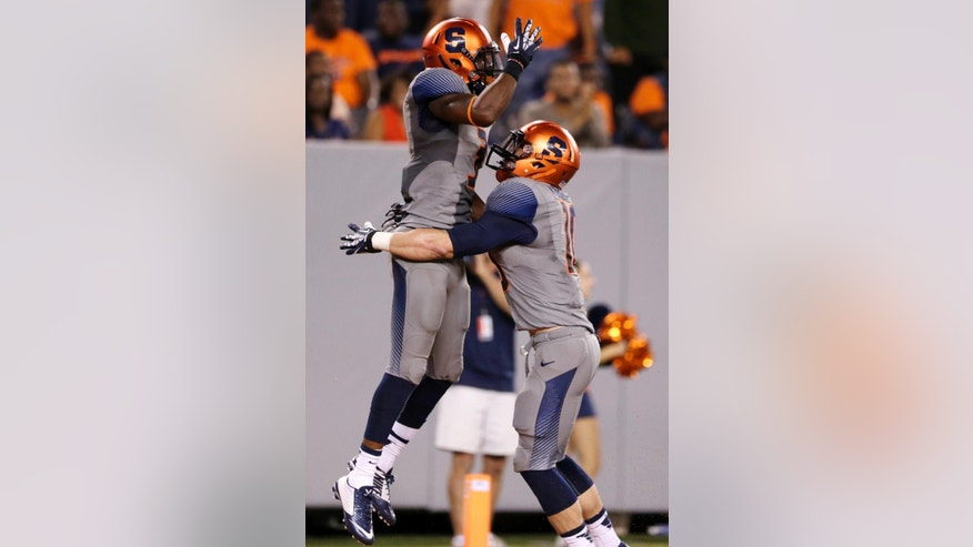 Syracuse safety Durell Eskridge, left, is congratulated by  Josh Kirkland after Eskridge scored on an interception during the second half of an NCAA college football game against Notre Dame, Saturday, Sept. 27, 2014, in East Rutherford, N.J. Notre Dame won 31-15. (AP Photo/Julio Cortez)