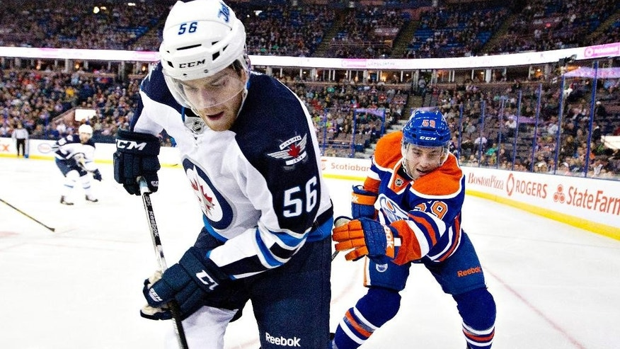 Winnipeg Jets Adam Lowry (56) and Edmonton Oilers Brad Hunt (59) battle in the corner during first period NHL hockey action in Edmonton, Alberta,  on Monday Sept. 29, 2014. (AP Photo/The Canadian Press, Jason Franson)