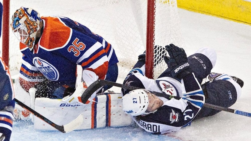 Winnipeg Jets Patrice Cormier (28) leaves the ice with an injury against the Edmonton Oilers during the third period of an NHL hockey game in Edmonton, Alberta on Monday, Sept. 29, 2014. (AP Photo/The Canadian Press, Jason Franson)