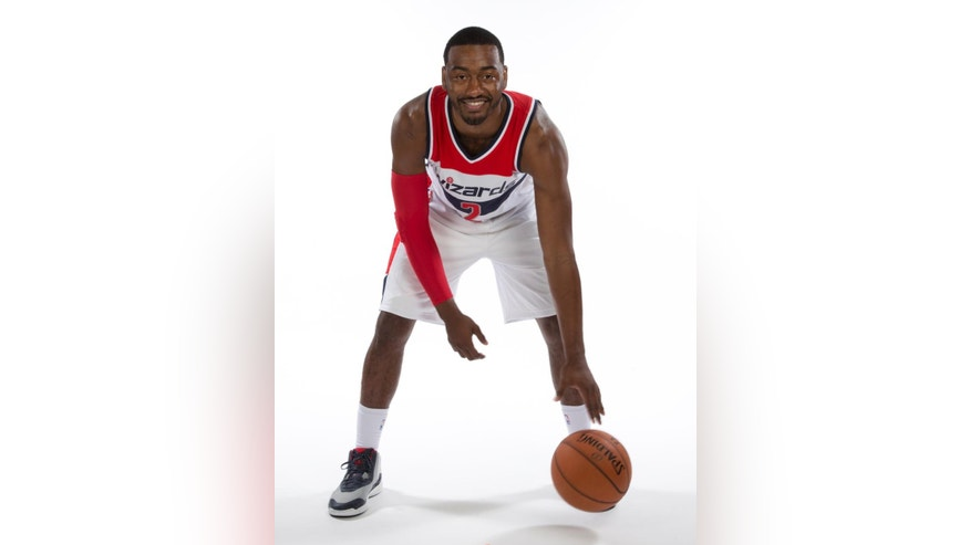 Washington Wizards guard John Wall (2) poses for photographs during NBA basketball media day at the Verizon Center in Washington, Monday, Sept. 29, 2014. (AP Photo/Carolyn Kaster)