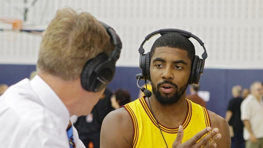 Cleveland Cavaliers' Kyrie Irving does a radio interview during the NBA basketball team's media day Friday, Sept. 26, 2014, in Independence, Ohio. (AP Photo/Mark Duncan)