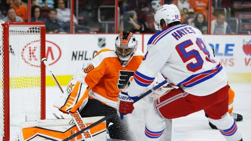 Philadelphia Flyers' Ray Emery, left, blocks a shot by New York Rangers' Kevin Hayes during the first period of a preseason NHL hockey game, Tuesday, Sept. 30, 2014, in Philadelphia. (AP Photo/Matt Slocum)