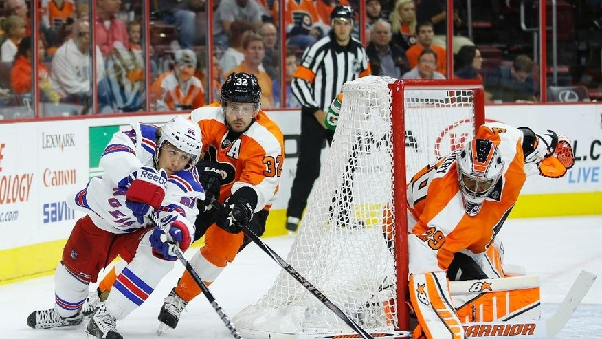 New York Rangers' Carl Hagelin, left, of Sweden, tries to get a shot past Philadelphia Flyers' Mark Streit, center, of Switzerland, and Ray Emery during the first period of a preseason NHL hockey game, Tuesday, Sept. 30, 2014, in Philadelphia. (AP Photo/Matt Slocum)