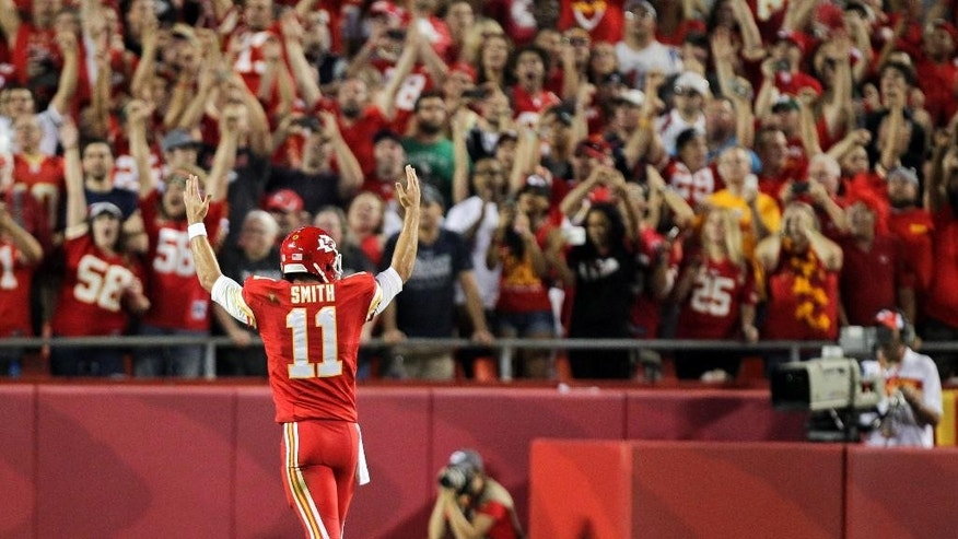 Kansas City Chiefs quarterback Alex Smith celebrates after a 2-yard touchdown run by Chiefs running back Jamaal Charles during the first quarter of an NFL football game against the New England Patriots, Monday, Sept. 29, 2014, in Kansas City, Mo. (AP Photo/Ed Zurga)
