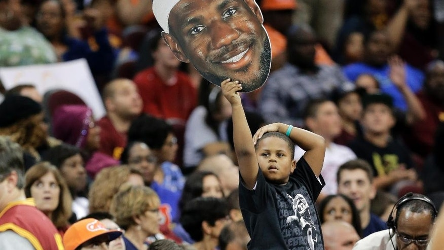 A Cleveland Cavaliers fan holds up a cutout of LeBron James during an NBA scrimmage basketball game Wednesday, Oct. 1, 2014, in Cleveland. (AP Photo/Tony Dejak)