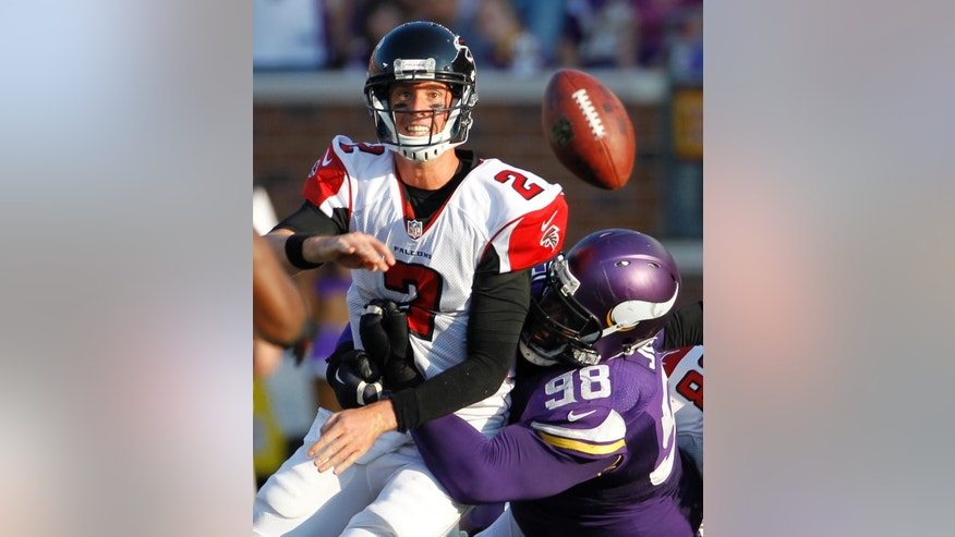 Atlanta Falcons quarterback Matt Ryan (2) passes the ball as he is hit by Minnesota Vikings defensive tackle Linval Joseph (98) during the second half of an NFL football game, Sunday, Sept. 28, 2014, in Minneapolis. (AP Photo/Ann Heisenfelt)