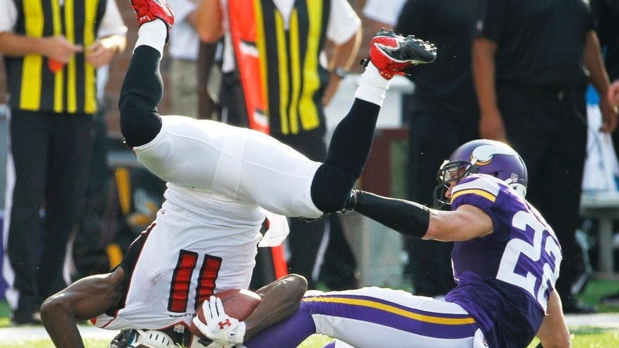 Atlanta Falcons wide receiver Julio Jones (11) is tackled by Minnesota Vikings free safety Harrison Smith during the first half of an NFL football game, Sunday, Sept. 28, 2014, in Minneapolis. (AP Photo/Ann Heisenfelt)