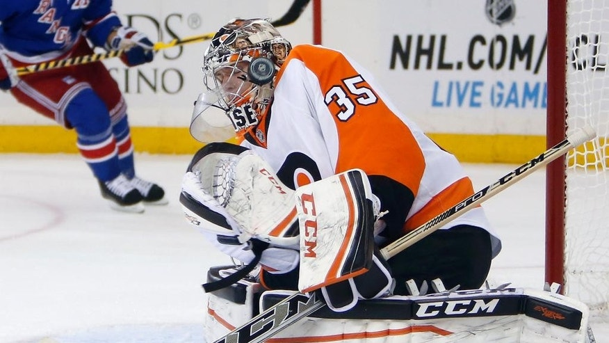 Philadelphia Flyers goalie Steve Mason (35) deflects a shot during the second period of an NHL preseason hockey game against the New York Rangers, Monday, Sept. 29, 2014, in New York. (AP Photo/Jason DeCrow)