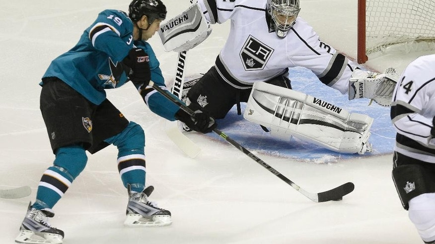 San Jose Sharks center Joe Thornton, left, scores against Los Angeles Kings goalie Jonathan Quick (32) during the first period of an NHL preseason hockey game in San Jose, Calif., Tuesday, Sept. 30, 2014. (AP Photo/Jeff Chiu)