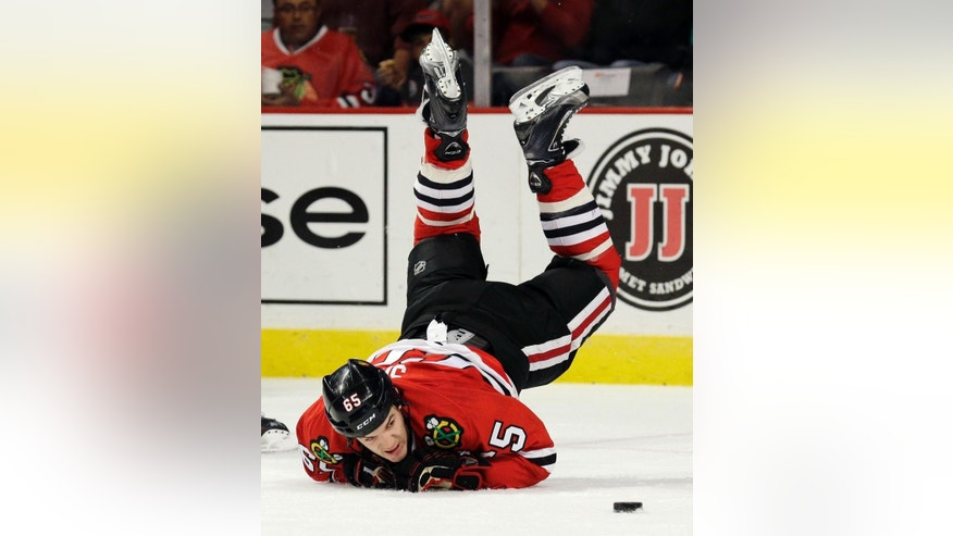 Chicago Blackhawks center Andrew Shaw (65) falls down on the ice during the second period of a preseason NHL hockey game against the Montreal Canadiens in Chicago, Wednesday, Oct. 1, 2014. (AP Photo/Nam Y. Huh)