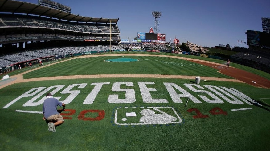 Bert McMenamim paints a postseason logo on the field before batting practice in Anaheim, Calif., Wednesday, Oct. 1, 2014. The Los Angeles Angels play Game 1 of the best-of-five AL division series against the Kansas City Royals on Thursday. (AP Photo/Chris Carlson)